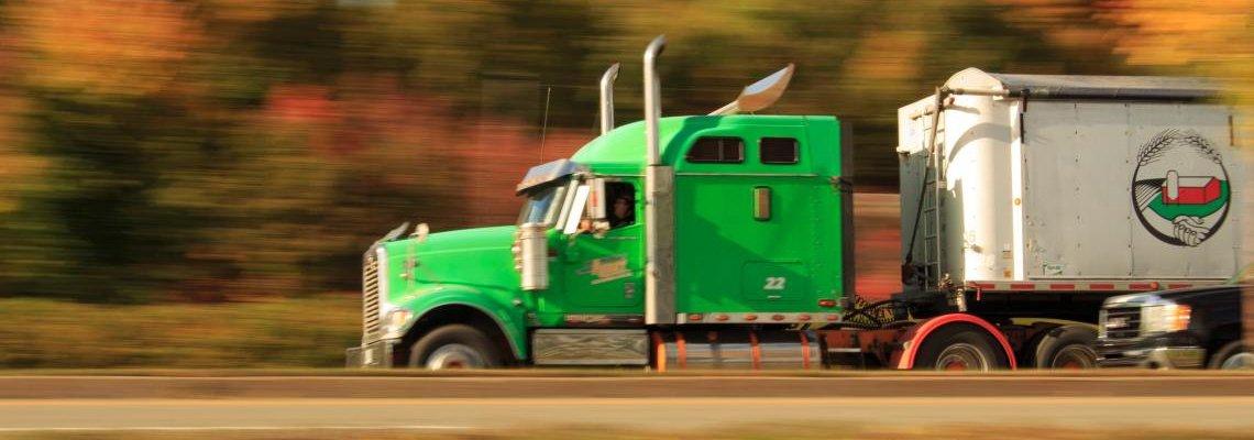 Green semi-truck driving fast down a road