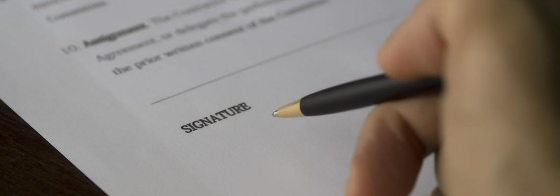 Hand signing a document with a pen