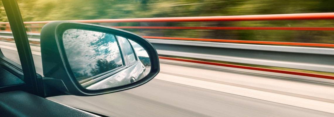 Close up of a rear-view mirror in car while driving fast