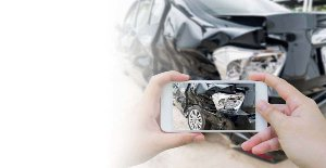Person holding a phone and taking pictures of wrecked car