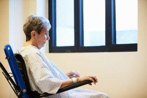 Elderly woman in a wheelchair and hospital gown