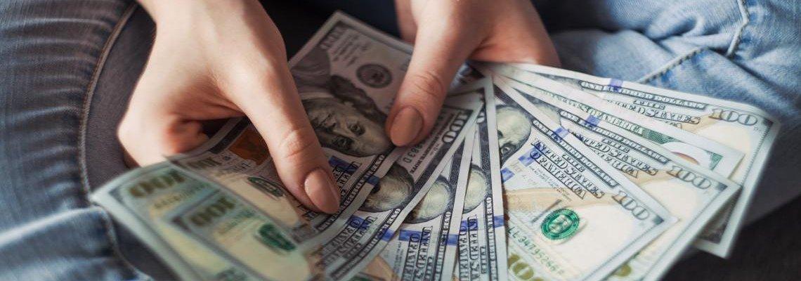 Person holding multiple one-hundred dollar bills
