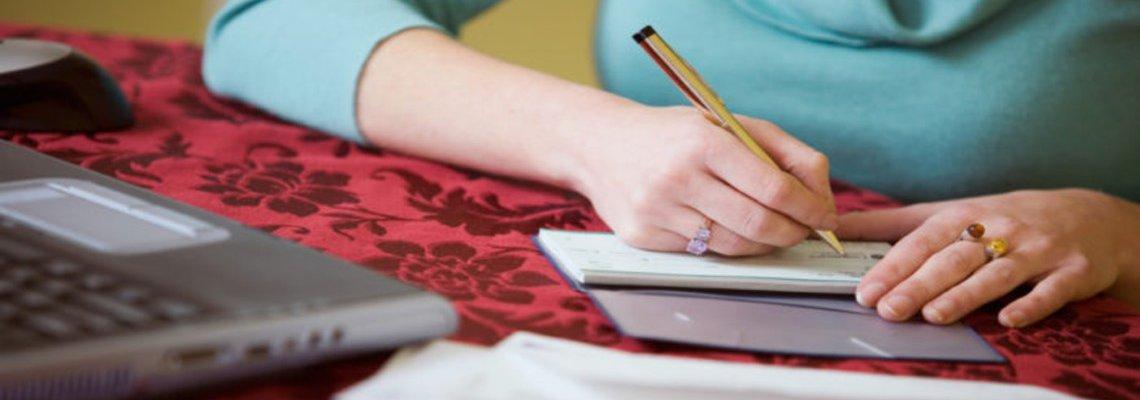 Woman writing checks by a laptop