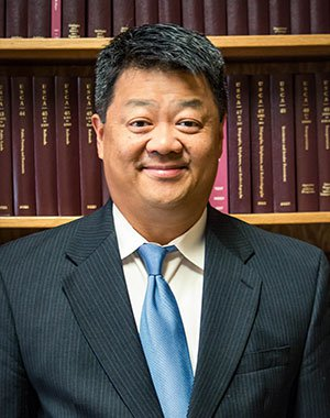 Headshot of Attorney Matthew H. Crow in front of the Bookshelves