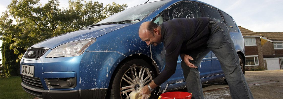 Man washing his car tires