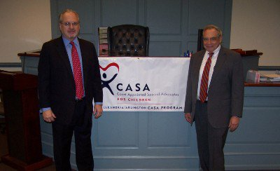 "Mark and David in Front of ""Court Appointed Special Advocates for Children"" Banner"