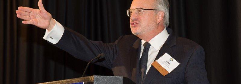 Mark Speaking at a Podium