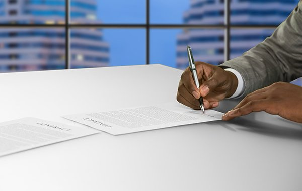 Man writing up a bunch of contracts