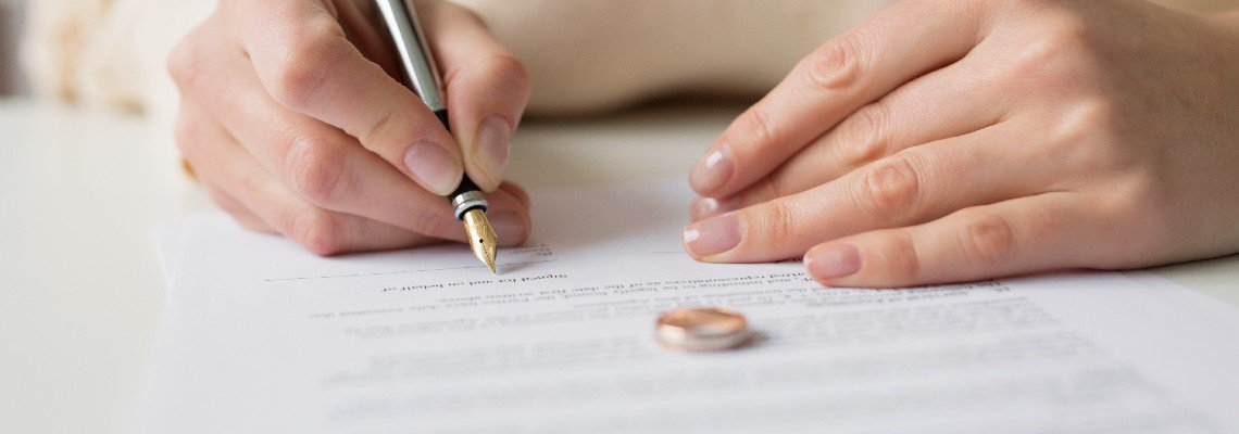 Person signing divorce papers with their wedding ring laid out on the document