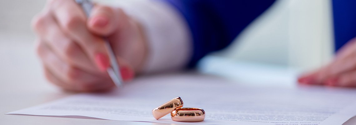 Woman Hands Signing Paper with Rings on It