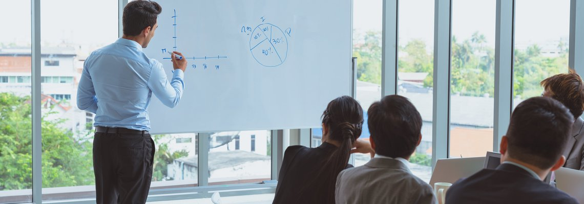 person in dress clothes drawing on white board for conference room