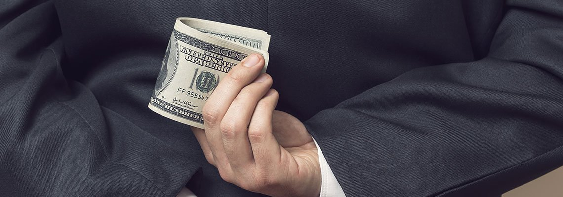 Man holding a cash behind his back with his finger crossed