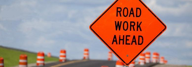 Road work ahead sign on road with cones along it