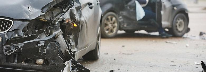 Two cars after an accident, man in passenger seat on the phone in the background