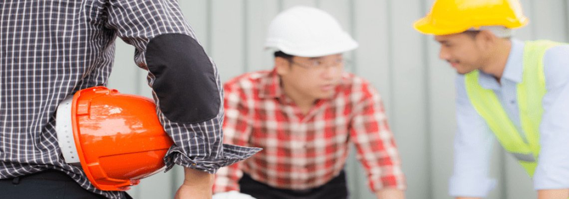 Three construction workers speaking to each other