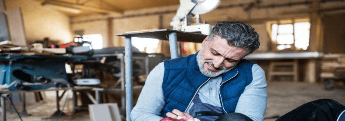 Man in a workshop treating his cut arm