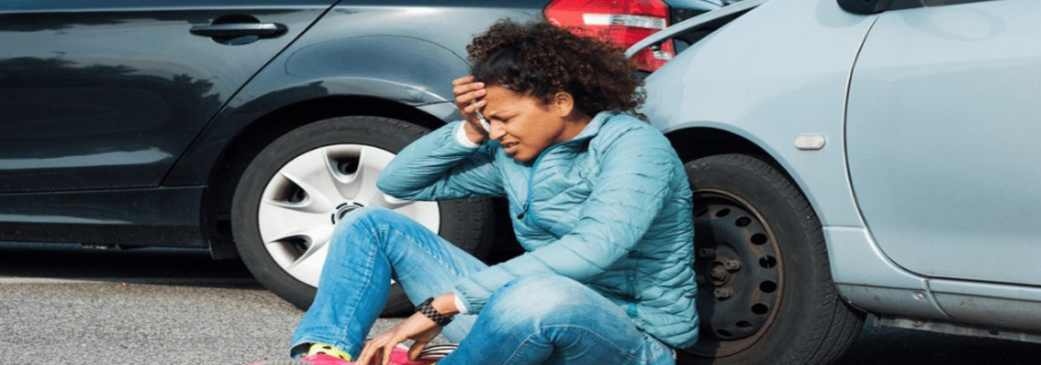 Woman distressed on the ground leaning against her car right after a fender bender