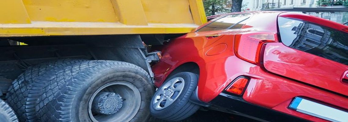 Small red car jammed underneath a large truck