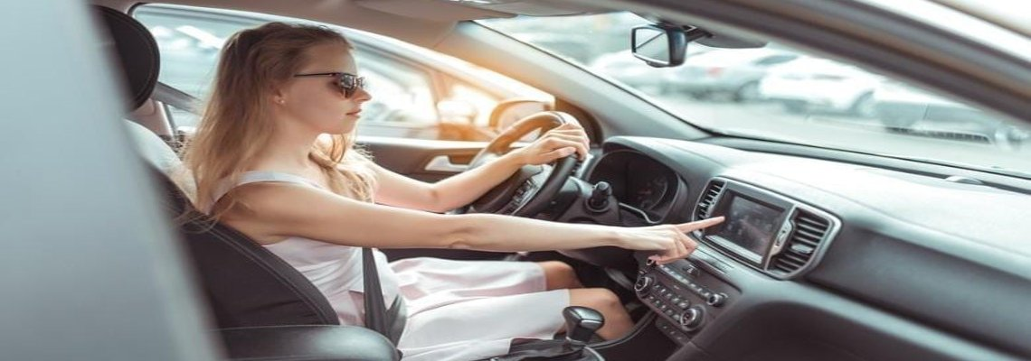 Woman in sunglasses pressing her car's dashboard