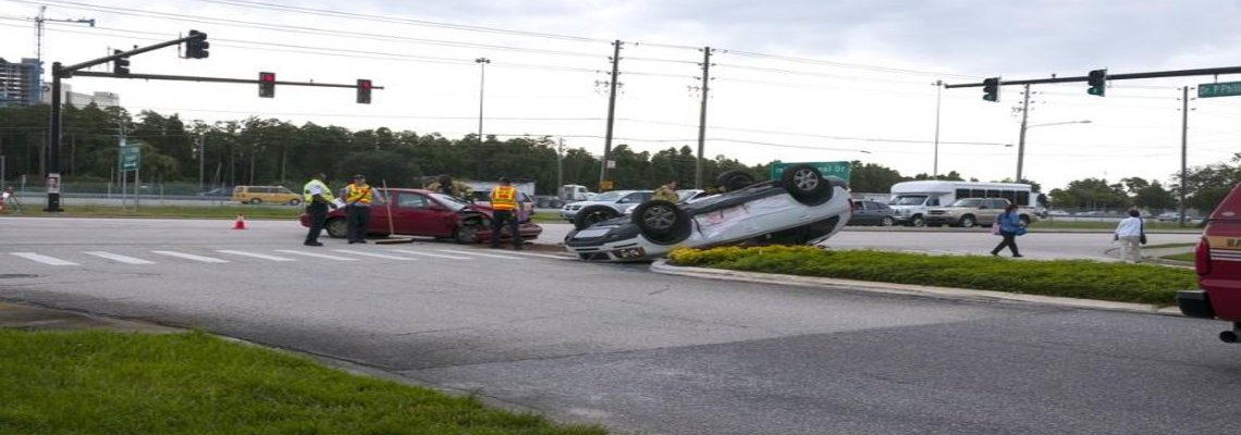 Accident at an intersection. Upside down white car and a black car