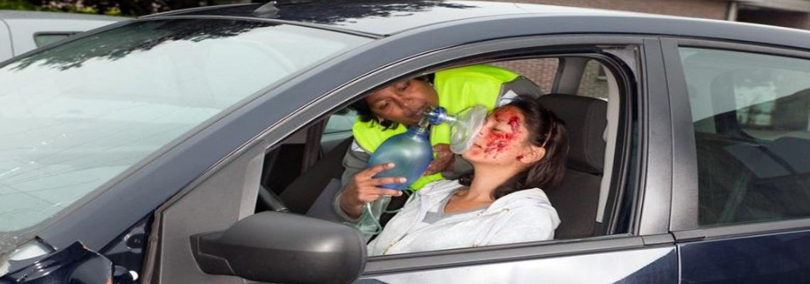 Bloodied woman in a car being treating with oxygen