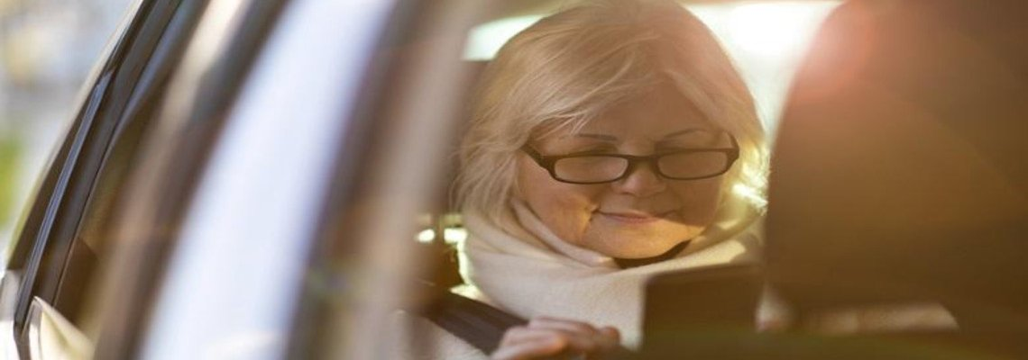 Woman in the backseat of a car using her phone