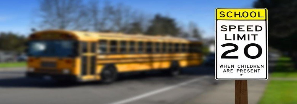 School Bus and an in focus Speed Limit sign