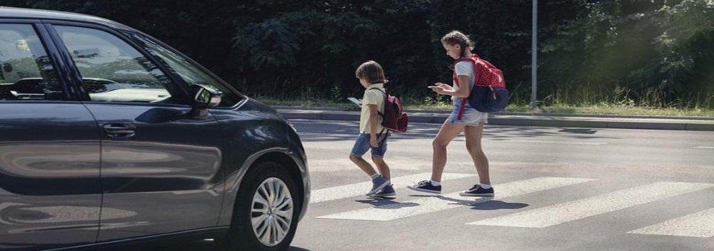 Two kids walking across a crosswalk while looking at their phones