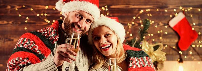 Couple holding champagne while dressed for Christmas