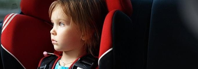young girl in a car seat looking out the window
