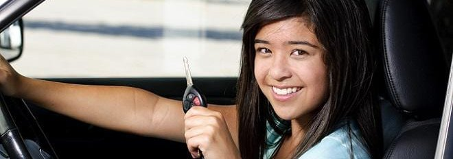 Women in driver's seat of car smiling and holding up the car key