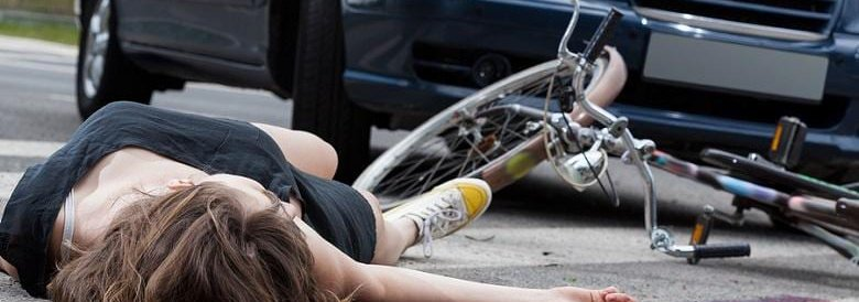woman lying on street next to bicycle and car