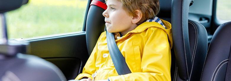 Young boy in car seat in the backseat of a car looking out window