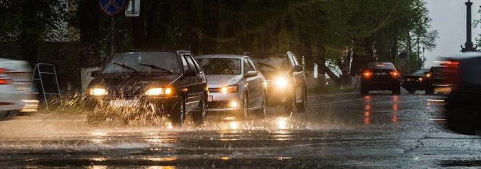 Three cars driving close together in a line while its raining