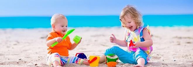 young boy and girl playing in the sand with buckets and shovels on the beach