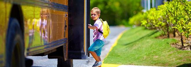 Young boy with yellow backpack getting onto school bus