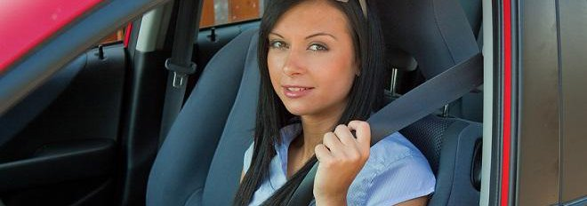 Brunette woman sitting in the drivers side of a pink car with hand on seatbelt