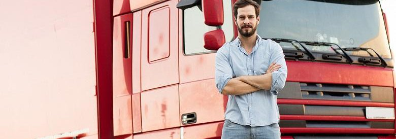 Bearded Man in button down and jeans standing in front of red semi truck with his arms crossed