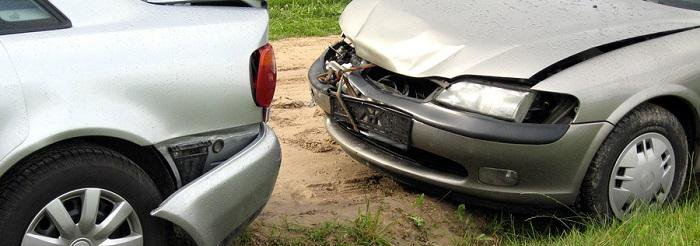 Two cars, a gray car in front with damage on the back and a tan car behind it with damage to the front of the car