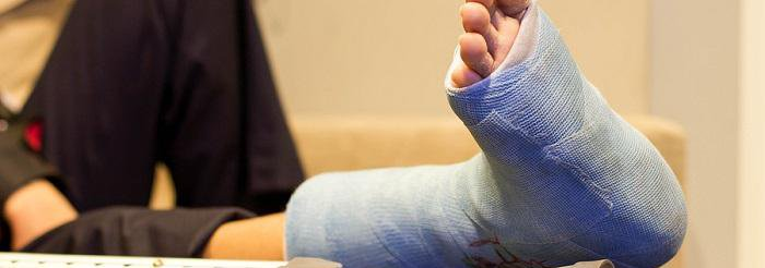 Close up of person's foot in a blue cast and a crutch lying down parallel to the leg