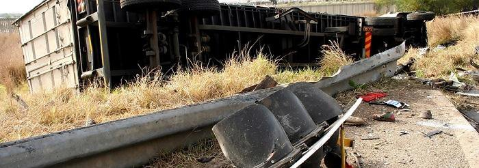 Truck tipped on its side next to a dented guard rail and pieces of debris scattered