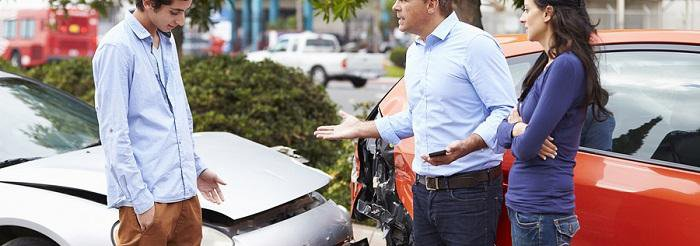Three people standing in front of two cars after an accident
