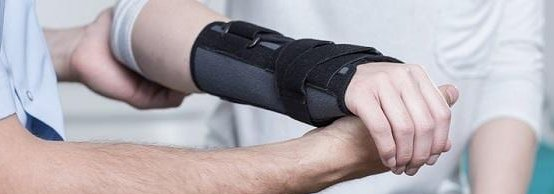 Close up of a person's wrist in a black brace being helped by a man