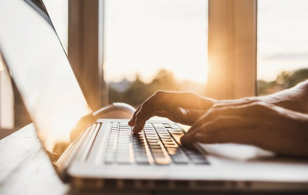 Man typing on computer with sun shining in the background