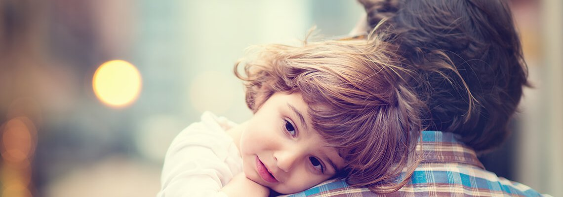 Little girl resting head on man's shoulder