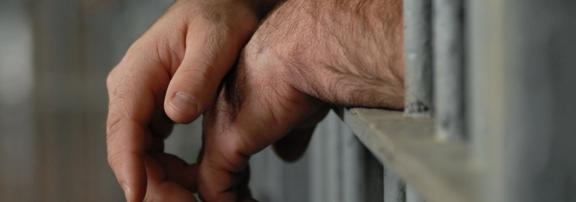 Hands leaning on jail cell bars