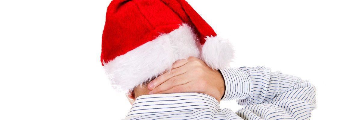 Man in santa hat rubbing neck