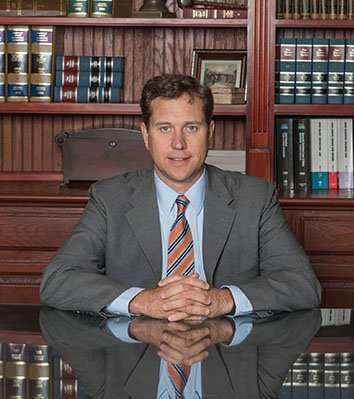 Attorney Martin E. Hubbell Sitting in front of the Bookshelves