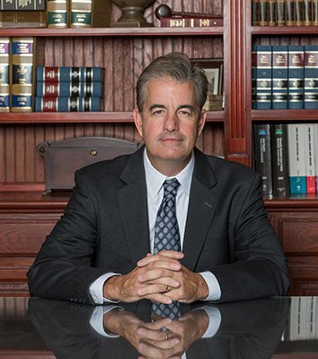 Attorney Thomas J. Diehl Sitting in front of the Bookshelves