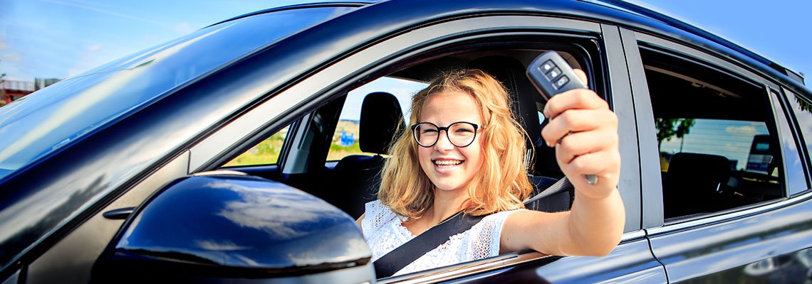 Teen Girl in the driver's seat showing off the car keys